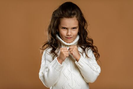angry screaming little child girl in white sweater mad raising fist frustrated and furious. Human emotions and facial expression Stock Photo