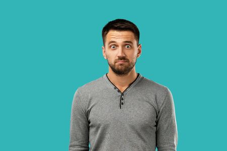 Portrait of young frowned handsome bearded man on blue background. facial expression Imagens