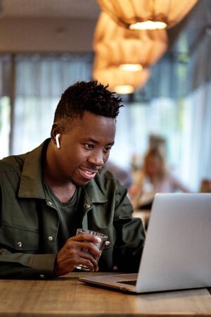 Cheerful young african american man in headphones using computer in cafe