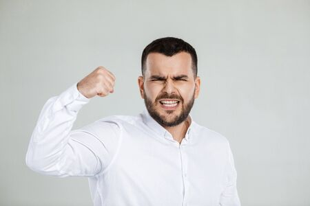 portrait of angry bearded man on gray background. Stock Photo