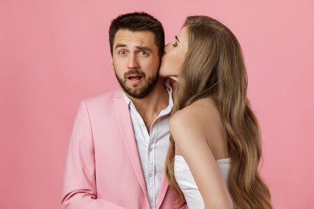 woman kissing her boyfriend. close-up. st valentines day. funny happy couple in love on pink background.