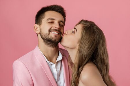 woman kissing her boyfriend. close-up. st valentines day. funny happy couple in love on pink background. Stock Photo - 137483238