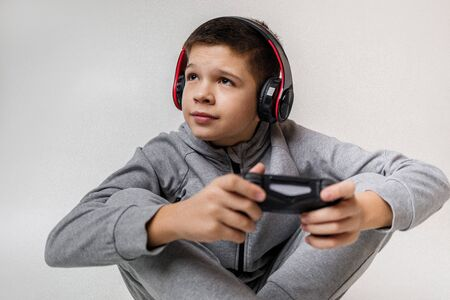 child boy playing video games over gray background. young gamer playing with game console Archivio Fotografico