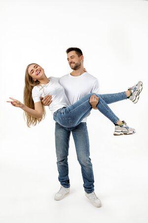 homme tenant petite amie sur ses bras sur fond blanc