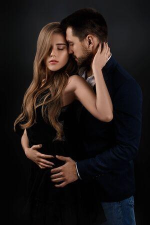 coppia elegante su sfondo nero. uomo che abbraccia una bella donna in abito nero Archivio Fotografico