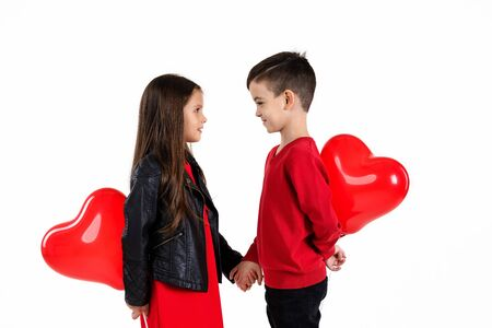 Happy kids with red heart balloon isolated on white background. child boy and girl want to exchange heart shaped balloons. St. Valentines Day Foto de archivo - 138469442