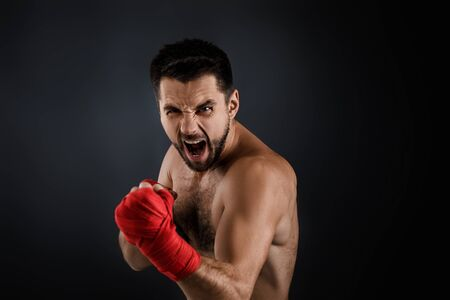 Sportsman boxer throwing a fierce and powerful punch. muscular man with red bandage on hands on black background.