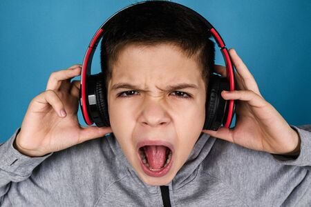 emotional child boy listens to music in headphones over blue background. close up