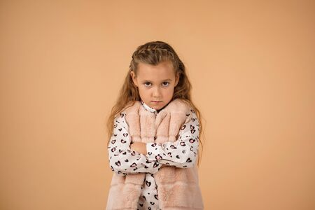 offended sad little child girl on beige background. Human emotions and facial expression