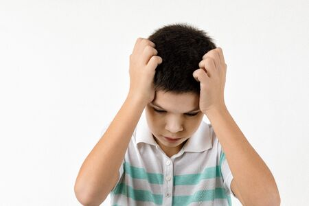offended sad little child boy in striped t-shirt on white background. Human emotions and facial expression