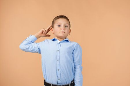Cute little child boy in blue shirt showing a saluting gesture on beige background. Human emotions and facial expression 스톡 콘텐츠