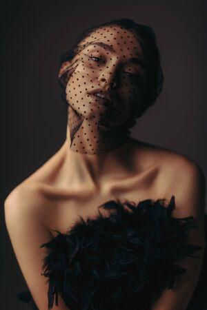 Modeporträt des eleganten Mädchens der Schönheit, das im schwarzen Schleier auf dunklem Hintergrund posiert. wunderschöne stilvolle Modellfrau im schwarzen Kleid mit Federn. Kreatives Kunstkonzept des schwarzen Schwans oder des dunklen Engels Standard-Bild