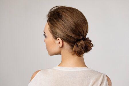 cute woman with beautiful elegant hair bun on gray background