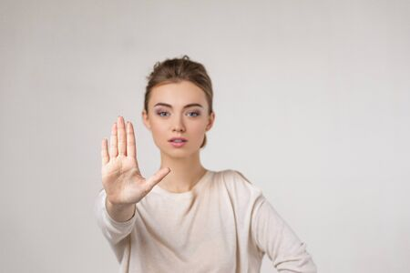 beautiful young woman making stop gesture on gray background.