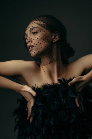 fashion portrait of beauty elegant girl posing in black veil on dark background. gorgeous stylish model woman in black dress with feathers. Art creative concept of black swan or dark angel