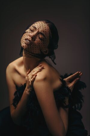 fashion portrait of beauty elegant girl posing in black veil on dark background. gorgeous stylish model woman in black dress with feathers. Art creative concept of black swan. woman has swan wings 免版税图像 - 140082165