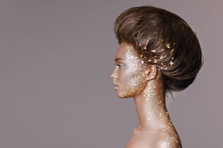Fashion art portrait of model girl with holiday golden shiny professional makeup. woman with gold metallic body and hair on gray background. Gold glowing skin. copy space Stock Photo