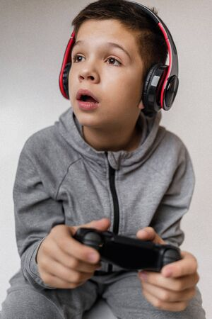 child boy playing video games over gray background. young gamer playing with game console. Someone distracts a guy from playing games Banco de Imagens