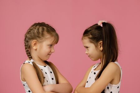 two angry little girls in dress looking at each other on pink background. childrens grievances and quarrels