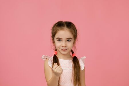 angry little child girl in dress raising fist frustrated and furious. Human emotions and facial expression Stock Photo