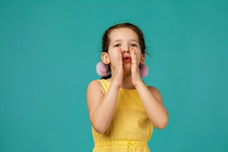 child calling someone. cute little girl shouting and holding her hand near her mouth on studio yellow background 스톡 콘텐츠