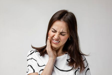 young sad woman suffering from tooth pain, caries. girl having toothache. Dental health and care concept