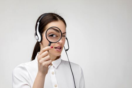 search concept. Beautiful woman consultant of call center in headphones holding magnifying glass on gray background. female customer support operator with headset. I will help find everything