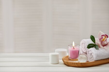 Spa products with aromatic candles, orchid flower and towel on white wooden table. Beauty spa treatment and relax concept. copy space Stock Photo