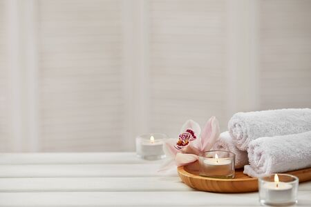 Spa composition with aromatic candles, orchid flower and towel on white wooden table. Beauty spa treatment. copy space Stock Photo