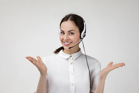 Beautiful smiling woman consultant of call center in headphones on gray background. female customer support operator with headset Stock Photo