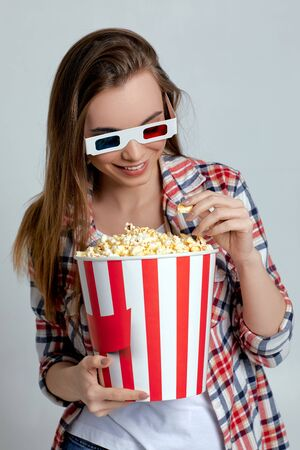 beautiful caucasian woman wearing red-blue 3d glasses and eating popcorn from bucket isolated on gray background