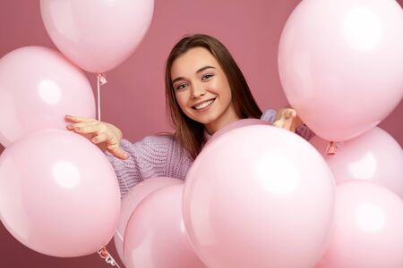 Smiling pleased girl posing with pastel pink air balloons on pink background. Beautiful happy young woman on a birthday holiday. close-up