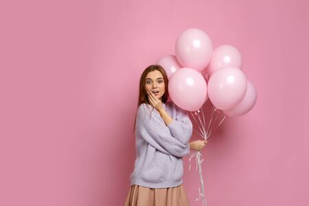 Smiling cute girl posing with pastel pink air balloons isolated over pink background. Beautiful happy young woman on a birthday holiday. space for text