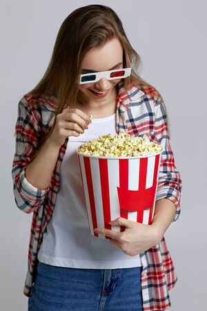 beautiful woman wearing red-blue 3d glasses and eating popcorn from bucket isolated on gray background 版權商用圖片