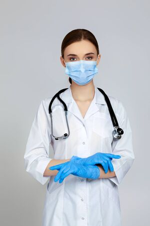 Portrait of beautiful woman doctor in white lab coat, mask and rubber gloves and stethoscope isolated on gray background