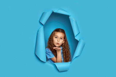 Portrait of cute happy smiling curly caucasian little cild girl sending kiss in blue paper hole.