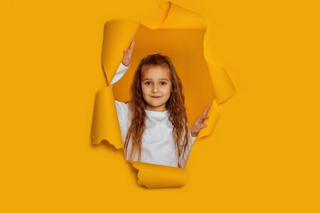 Portrait of cute happy smiling caucasian little cild girl poses in yellow paper hole.