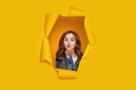 Portrait of cute happy smiling caucasian little cild girl sending kiss in yellow paper hole. Banco de Imagens