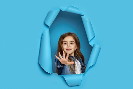 Portrait of cute happy smiling caucasian little cild girl stretches hand in front through blue paper hole.
