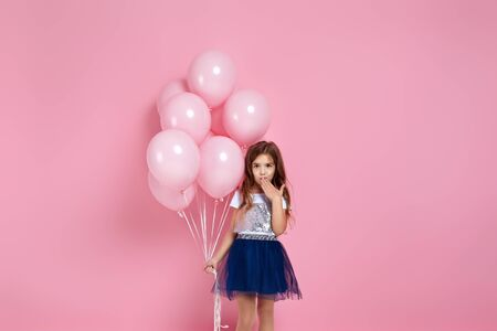 cute little child girl with pastel pink air balloons covering his mouth with hand isolated over pink background. OMG. kid forgot a gift for birthday party. copy space