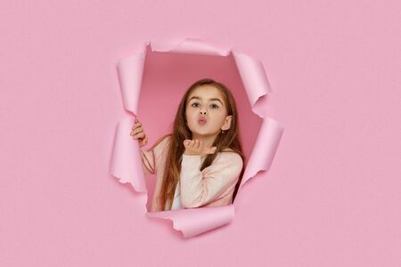 Portrait of cute happy smiling caucasian little cild girl sending kiss in pink paper hole.