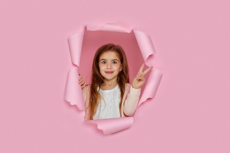 Portrait of cute happy smiling caucasian little cild girl showing victory gesture in pink paper hole.