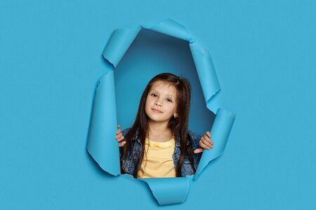 Portrait of cute happy smiling caucasian little cild girl poses in blue paper hole.