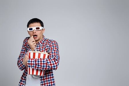 surprised handsome caucasian man wearing red-blue 3d glasses and eating popcorn from bucket while watching a horror movie isolated on gray background. copy space Foto de archivo