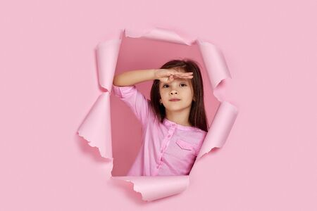 Portrait of cute caucasian little child girl looking far away with hand over head in torn paper pink wall. Searching concept.