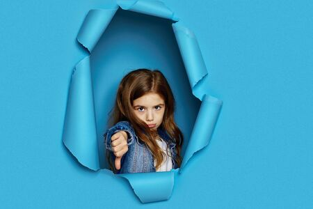 Portrait of cute caucasian little cild girl showing thumbs down in blue paper hole.