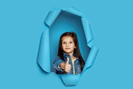 Portrait of cute happy smiling caucasian little cild girl showing thumbs up in blue paper hole. Banco de Imagens