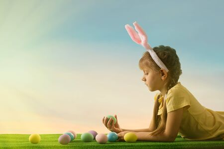 adorable little child girl with bunny ears on Easter day. kid with Easter eggs on the lawn. Foto de archivo
