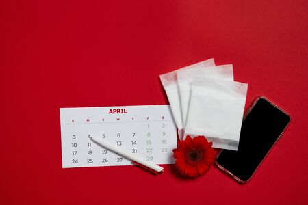 menstrual pads and red flower on red background, feminine calendar and cell phone with copy space. Care of hygiene during menstruation. top view. Imagens