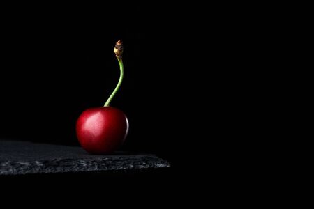 sweet ripe red cherry on black background with copy space Imagens